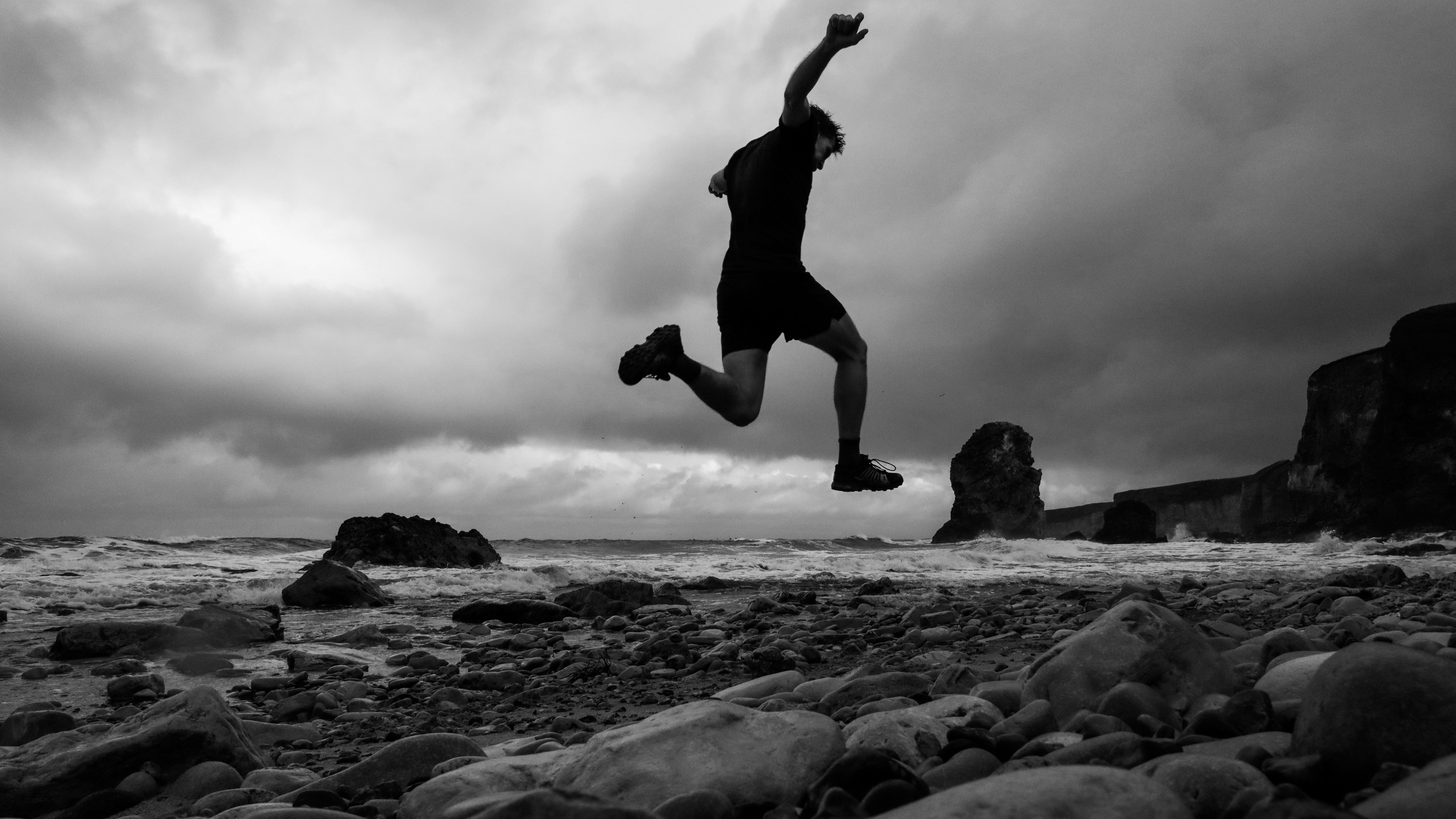 A low-angle shot shows a man in the air as he runs on a rocky beach.